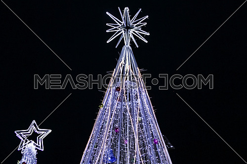 Low Angel for Chrismas tree with lights and stare shape at night