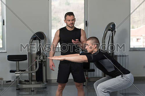 Personal Trainer Showing Young Man How To Train On Bosu Balance Ball In A Gym