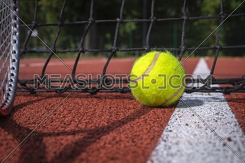 Shadows of racket and net surrounding a tennis ball on a white line on an outdoor court in sunshine in a sport and active lifestyle concept