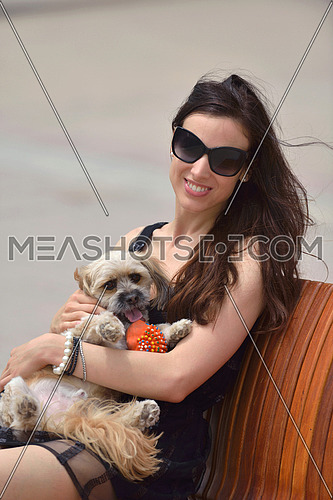 beautiful happy young  woman in black dress with cute small dog puppy have fun on street