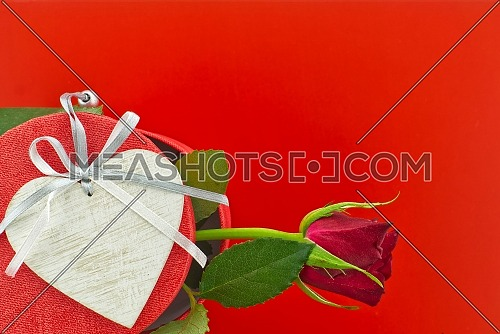Single rose on gift box and heart medallion over red background with free copy space