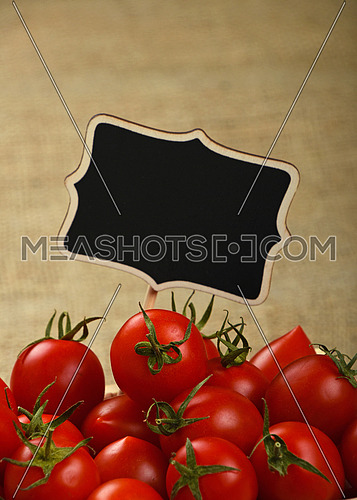 Red ripe fresh small cherry tomatoes with black wooden chalkboard price sign tag close up over jute burlap canvas background