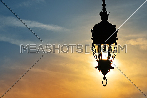 Close up side view of old vintage antique street lamp lantern over bright evening sunshine and vivid sunset sky