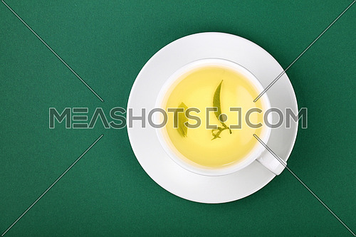 Close up one full white cup of green oolong tea with leaf, on saucer on green table background, elevated top view, directly above