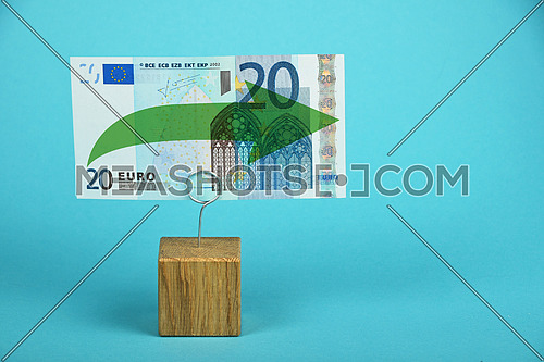 Stagnation and support of European economy and Euro currency, twenty Euro banknote with green horizontal arrow on holder over blue background
