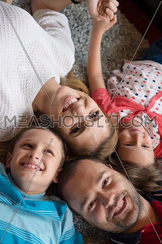 Top view of beautiful young parents, their cute little daughter and son holding hands, looking at camera and smiling, lying on the floor