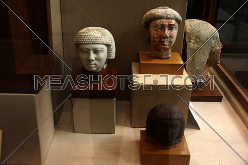 a photo from inside the Egyptian museum in Cairo showing a display of monumental pharaohs statues and faces