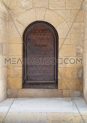 Wooden aged vaulted ornate door and stone wall at caravansary (Wikala) of Bazaraa, Medieval Cairo, Egypt