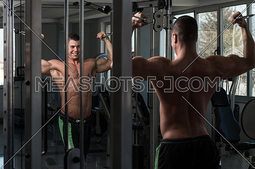 Young Bodybuilder Is Working On His Biceps With Cable Crossover In A Dark Gym