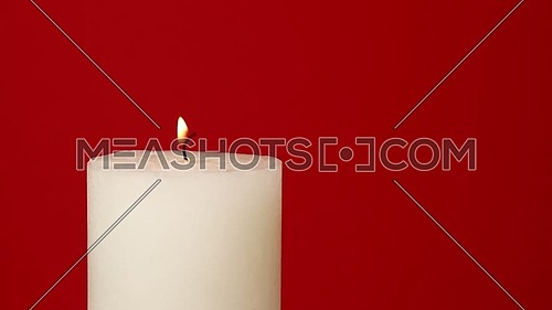 Close up one white candle trembling flame over vivid maroon red background, off-center, fired up with lighter, burning and blown out