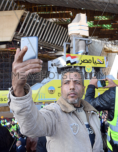 close shot for a man taking a selfie picture with The Statue of King Ramses II while the transferring process to the Grand Egyptian Museum in Cairo on 25 January 2018