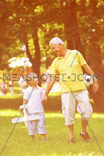 happy grandfather and child have fun and play in park