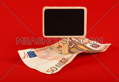 Close up one fifty Euro paper currency banknote and blank chalk blackboard sign with copy space over red background, low angle view