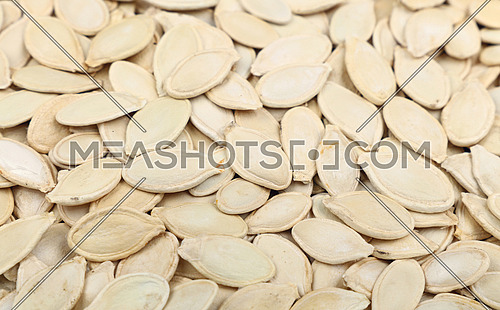 Background pattern of raw white pumpkin seeds (pepitas) close up, low angle view