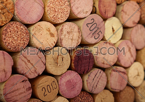 Close up background pattern of many assorted stacked used red wine corks