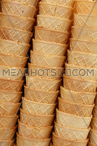 Background of empty fresh wafer ice cream cone cornet cups in row stacks, close up, low angle side view