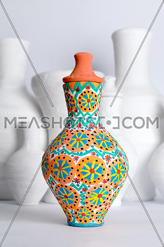 Egyptian decorated colorful pottery vase (arabic: Kolla) on blurred background of white vases