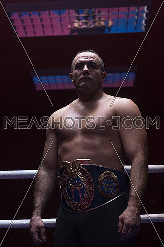 portrait of muscular professional kick boxer with his championship belt in the training ring