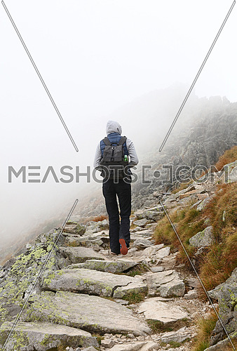 One young tourist woman with backpack walking up mountain road on foggy weather day, low angle rear view