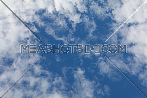 Beautiful cloudscape with bright white clouds over blue sky, low angle view
