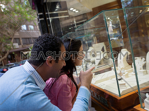 Young middle eastern happy couple enjoying while looking jewelry in the window of a luxury jewelry store