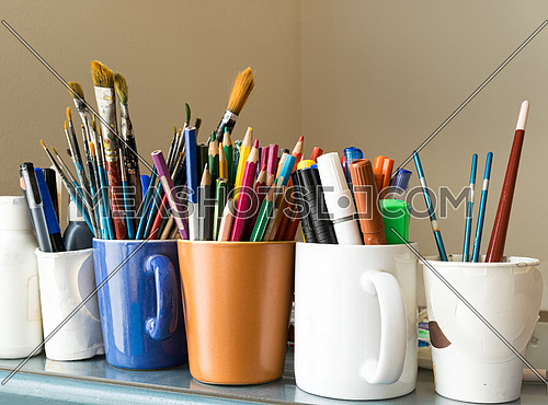 Close up of different used paint brushes, sharpened colored pencils, pens, and markers on colored mugs over blue table and beige background