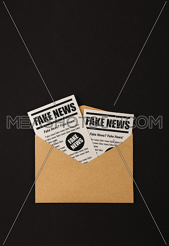 Close up brown paper mail envelope with FAKE NEWS newspapers over black background with copy space, elevated top view, directly above