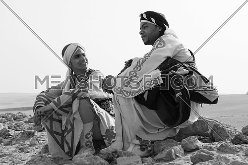 a black and white shot of two Egyptian sufi dancers sitting in the desert talking