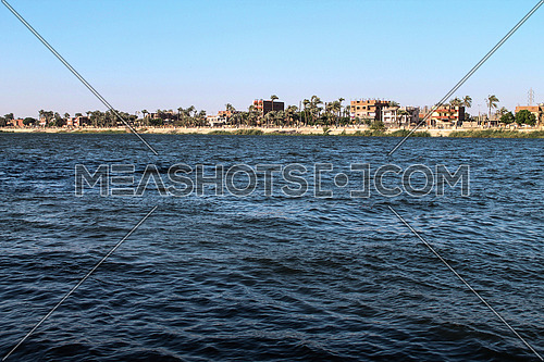 a photo for river Nile from one of upper Egypt Cities showing the other bank,  palm trees and cultivated areas