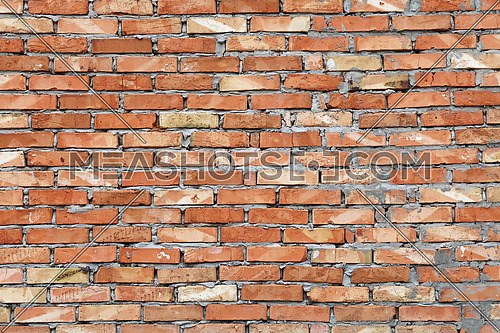 Rough red brown brick wall background texture close up, side view