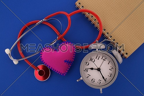 Medical concept with stethoscope and red heart, alarm clock and open wire bound notebook for your text