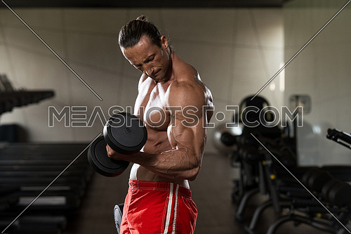 Muscular Mature Man Doing Heavy Weight Exercise For Biceps With Dumbbells In Modern Fitness Center