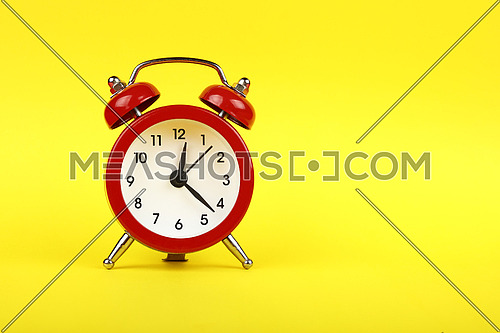 Close up one small red metal twin bell retro alarm clock over yellow paper background with copy space, low angle front view