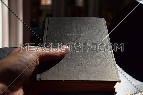 Man hand holding Holy Bible old vintage book in canvas hardcover over wooden pew during prayer in Christian catholic church or cathedral, close up, personal perspective
