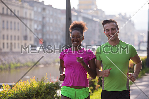 healthy young multiethnic couple jogging in the city at early morning with sunrise in background