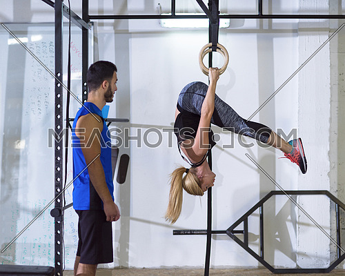 young athletic woman working out with personal trainer on gymnastic rings at the crossfitness gym