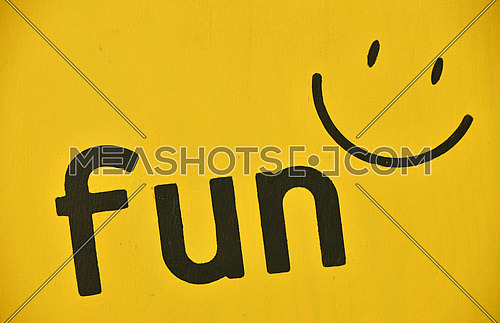 Word FUN and smile icon painted black on vivid yellow background, close up