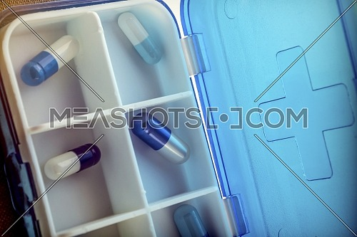Pillbox with capsules blue and white, conceptual image