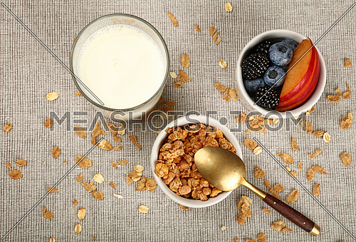 Close up portion of muesli granola breakfast with fruits and berries, with glass of milk, elevated top view, directly above