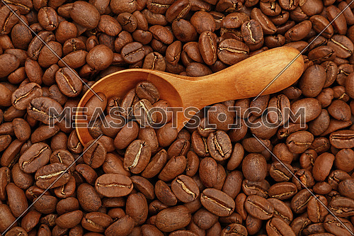 Close up wooden scoop with roasted coffee beans, elevated top view, directly above