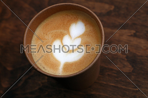Close up one latte cappuccino coffee to go, take away, in brown paper cup over background of wooden table, elevated high angle view