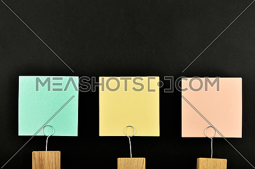 Three paper notes, green, yellow, pink, with wooden holder isolated on black paper background for presentation