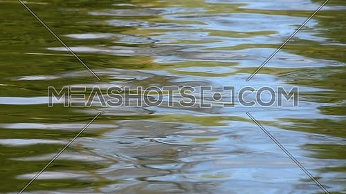 Colorful abstract background of blue and green ripples and waves running on water surface, moving flow background