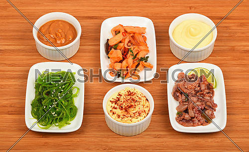 Three portions of seafood marinated salad with octopus cuttlefish, squid and seaweeds in white plates with sauce on wooden table, high angle view