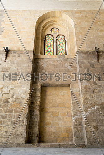 Recessed arched frames and two colored stained glass windows in an old stone bricks wall, Medieval Cairo, Egypt