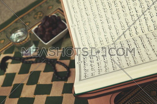Iftar time Dried Dates, Holy Quran glass of water and tasbih on praying  rug or sejadah in Ramadan concept of Islamic education