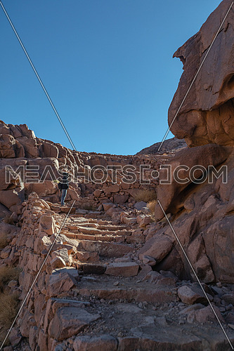 Long shot for stairs made of rock and a tourist standing on in Mount Sinai Egypt