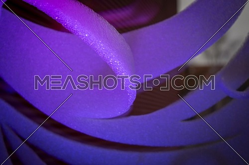 Close-up of violet abstract stripes of foamy material on dark background