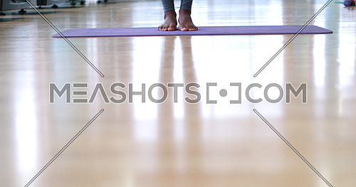 black woman standing on yoga mat with focus on bare feet