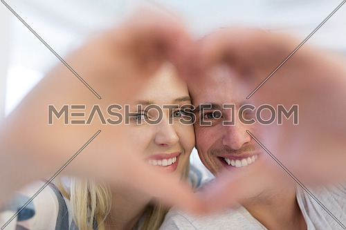 Young lovely couple making heart with hands at home